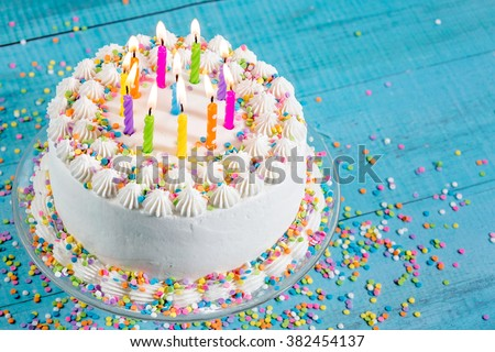 Birthday cake with colorful sprinkles and Candles over blue background - stock photo