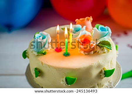 Birthday cake with lighted candles and marzipan roses - stock photo