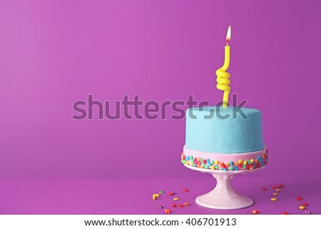 Birthday cake with one candle on purple background. - stock photo