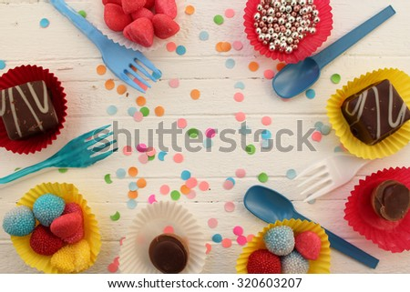 Birthday celebration cupcake, candy, plastic fork and spoon and confetti background - stock photo