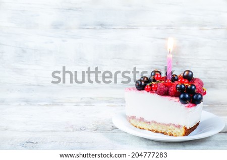 birthday cheesecake with candle, raspberries, red and black currants on a white wood background. toning. selective focus on candle - stock photo