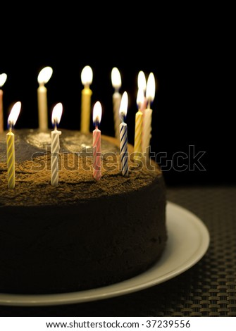 birthday chocolate cake with burning candle on the top. Black background and shallow depth of field. - stock photo