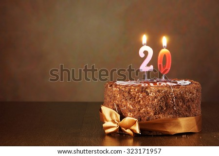 Birthday chocolate cake with burning candles as a number twenty on brown background - stock photo
