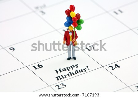 "Birthday concept. A miniature man holding a bunch of balloons is standing on a calendar date that says ""Happy Birthday."" - stock photo"