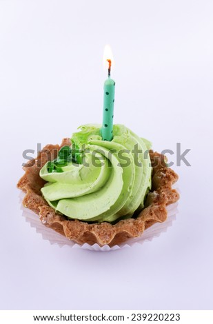 Birthday cup cake with candle on white background - stock photo