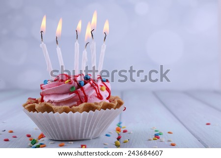 Birthday cup cake with candles and sparkles on color wooden table and light background - stock photo