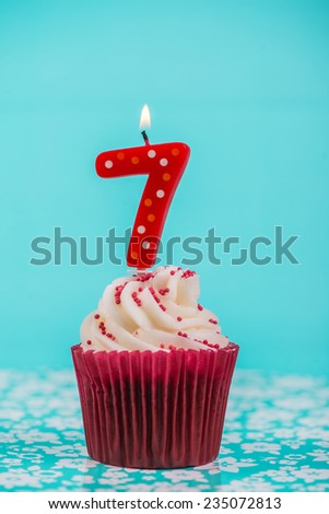 birthday cup cake with number seven candle on blue background - stock photo
