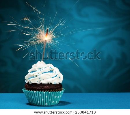 Birthday Cupcake with a sparkler over a blue background. - stock photo