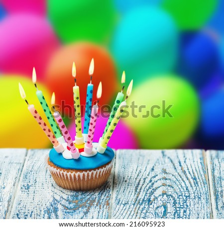 Birthday cupcake with burning candles on the background of balloons - stock photo