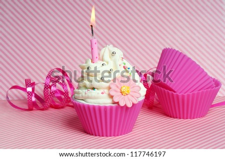 Birthday cupcake with candle and pink festoon - stock photo