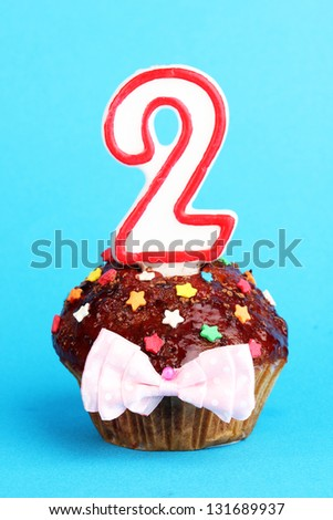 Birthday cupcake with chocolate frosting on blue background - stock photo