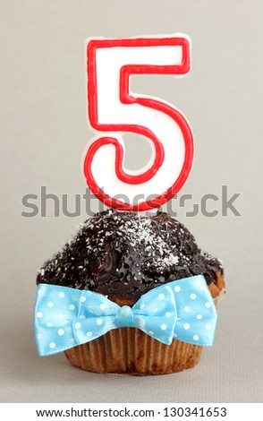 Birthday cupcake with chocolate frosting on grey background - stock photo