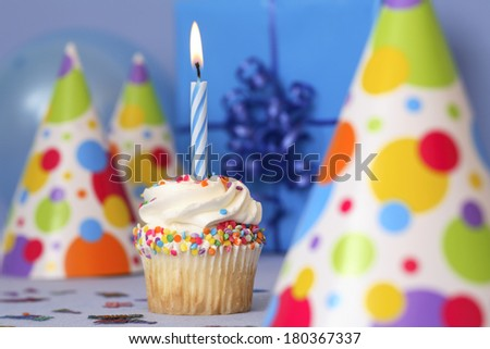 Birthday cupcake with lit candle on blue background  - stock photo
