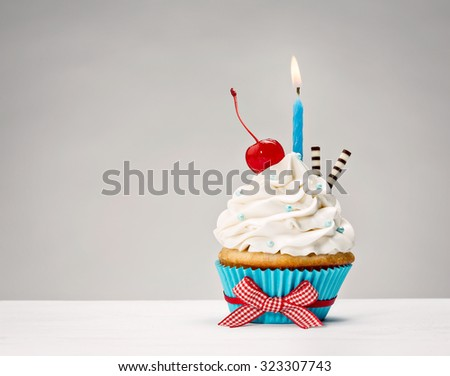 Birthday Cupcake with vanilla buttercream icing, candle and a cherry on top. - stock photo