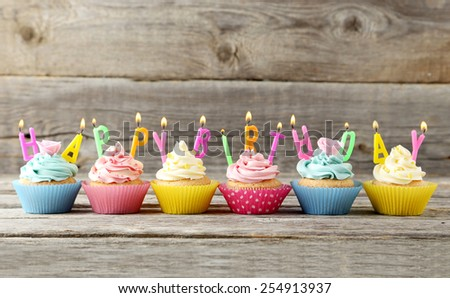 Birthday cupcakes with candles on grey wooden background - stock photo