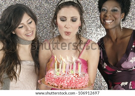Birthday girl blowing birthday cake's candles with friends. - stock photo