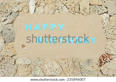 Birthday greetings written in a frame of white corals at the beach - stock photo