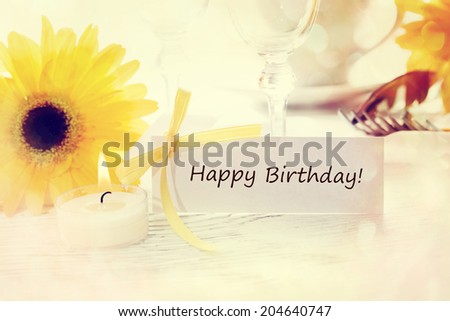 Birthday message card with table setting and yellow gerberas - stock photo