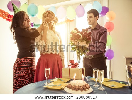 birthday party at home. couple and a friend celebrating with a surprise party - stock photo