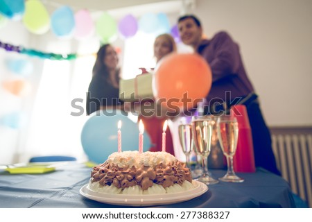 birthday party at home. three friends celebrating the girl birthday with surprise party at home. concept about birthday, party and people - stock photo