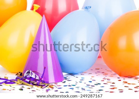Birthday party hat and balloons with confetti and a noisemaker - stock photo