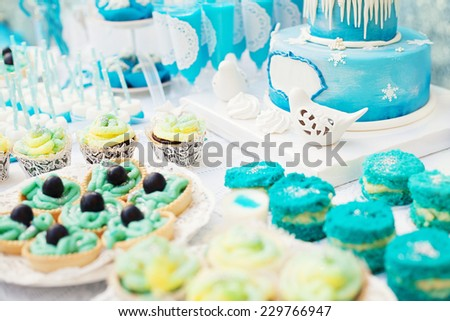 birthday party preparation with colorful cakes and sweets - stock photo
