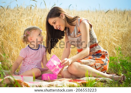 Birthday present box for little girl at grain field - stock photo