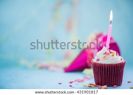 birthday wish cupcake with candle and party hat - stock photo