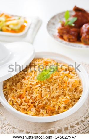 Biryani rice or briyani rice, curry chicken and salad, traditional indian food on dining table. - stock photo