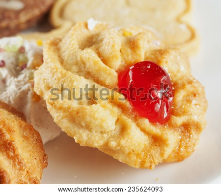 Biscuit with cherry over a white plate - stock photo