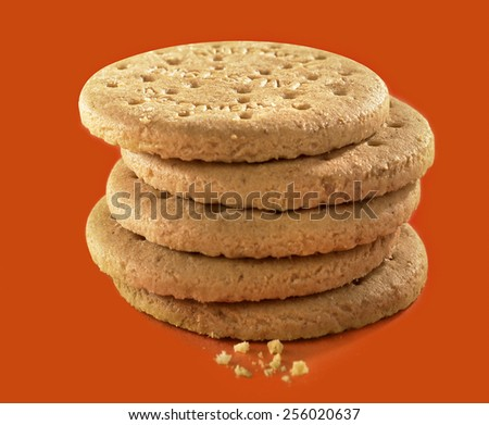 BISCUITS - A stack of digestive biscuits with a few crumbs at the front - stock photo