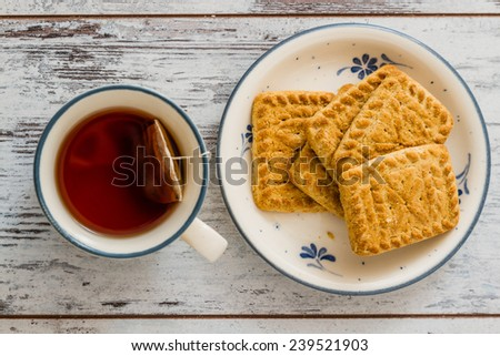 Biscuits and cup of tea on white wooden background - stock photo