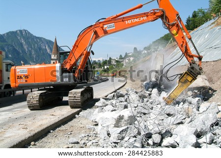 Bissone, Switzerland - 28 May 2008: Workers breaking up a wall with a Hydraulic digger on a highway at Bissone on Switzerland - stock photo