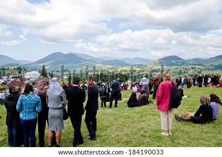 BISTRITA, ROMANIA - SEPTEMBER 8: Gathering of many people on a green lawn watching and listening on September 8th 2013 at Piatra Fantanele near Dracula Castle - stock photo