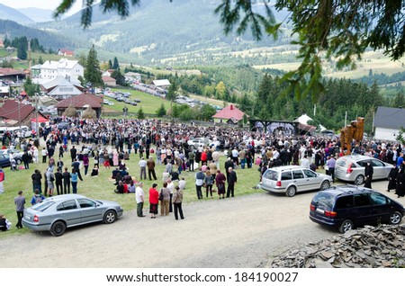 BISTRITA, ROMANIA - SEPTEMBER 8: Gathering of many people on a green lawn watching and listening to a religious ceremony happening on stage, Sept. 8th 2013 at Piatra Fantanele near Dracula Castle. - stock photo