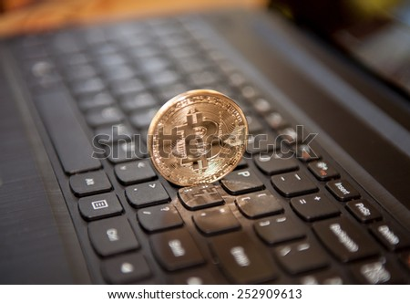 Bitcoin physical coin symbol on black keyboard - stock photo