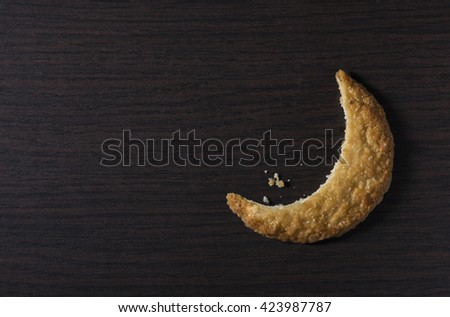 Bite of a cookie biscuit in moon shape. Moon-shaped cookie - creative idea. - stock photo