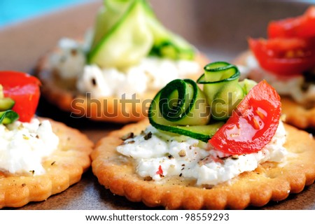 Bite size canapes with ricotta cheese, courgettei and tomato - stock photo