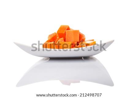 Bite sized papaya fruit on white plate over white background - stock photo