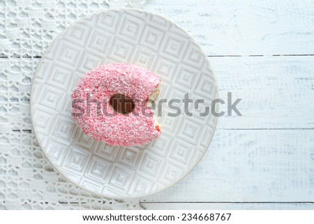 Bitten delicious donut on plate on wooden table close-up - stock photo