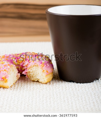 Bitten donut with pink glaze and many decorative sprinkles. - stock photo