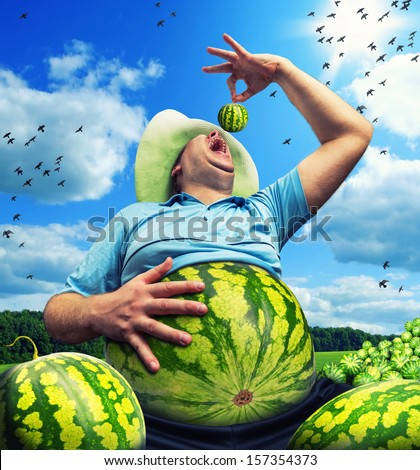 Bizarre farmer with watermelon instead of the abdomen on field in summer - stock photo