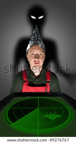 Bizarre man wearing a foil hat and watching old radar monitor with alien shadow behind - stock photo