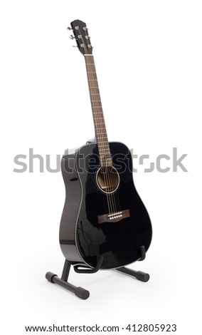 Black acoustic guitar on stand, isolated on a white background - stock photo