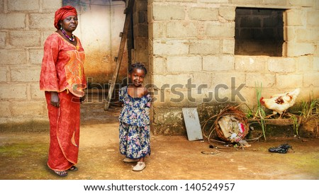 Black African little girl and her mother in traditional clothing at home - stock photo