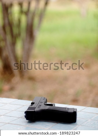 black air soft gun pistols model of a replica real pistol on an outdoor bench in green area in a garden of a country house - stock photo