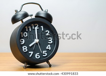 Black alarm clock place on wood table in burred background - stock photo