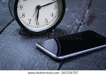 Black alarm clock with cell phone on a wooden table - stock photo