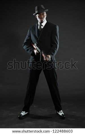 Black american mafia gangster man in suit with gun. - stock photo
