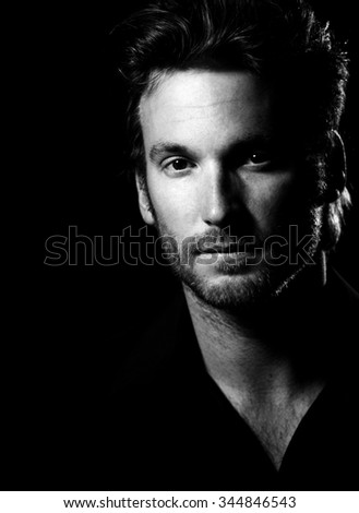 Black an white portrait of handsome mid-adult man wearing black, looking at camera confidently. - stock photo